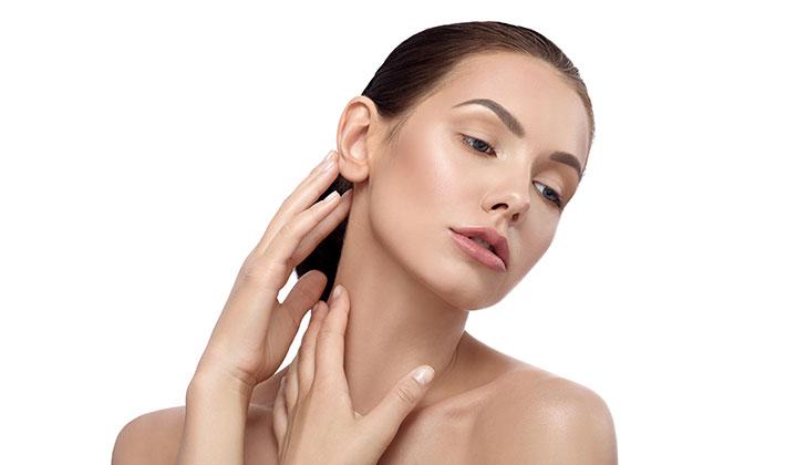 mulher branca, com cabelos castanhos, com as mãos ao redor do pescoço, mostrando jovialidade de sustentação da pele.
