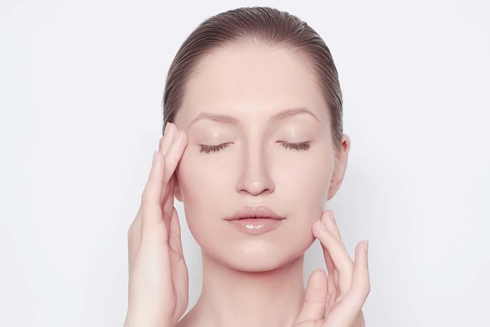 Foto de uma mulher branca, de cabelo castanho. Ela está com uma expressão de relaxamento, com os olhos fechados, enquanto suas mãos tocam delicadamente a face em ambos os lados.