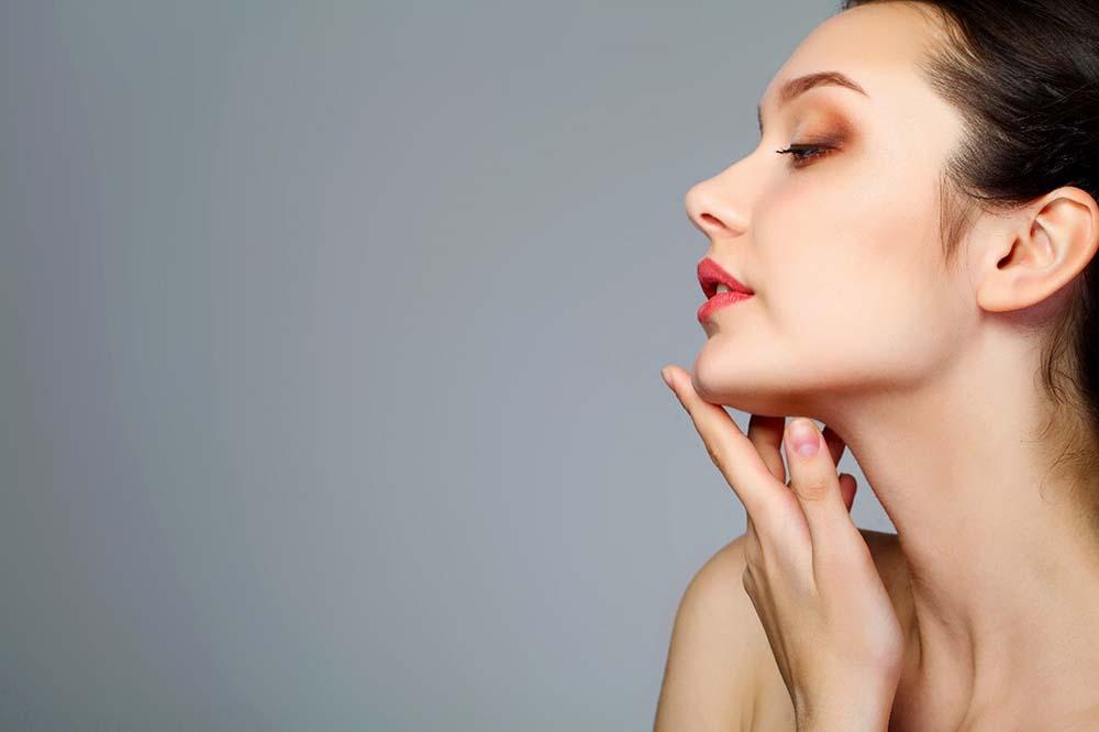 Mulher branca, de cabelo preto, com batom e maquiagem. Encontra-se de perfil e com a mão esquerda posicionada logo abaixo do rosto, com o dedo indicador encostando no queixo.