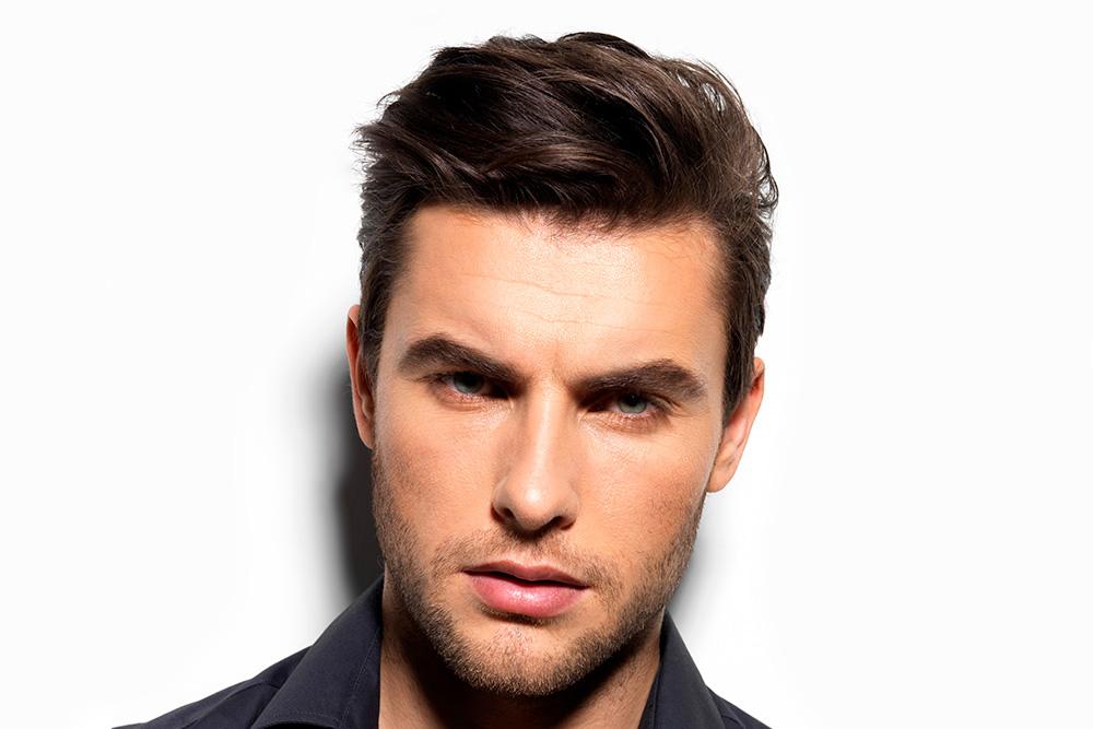 Um homem de pele branca, olhos claros e cabelo preto está centralizado na imagem. Ele está com expressão neutra.
