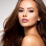 Uma mulher jovem, de cabelos castanhos, olhos marrons de tonalidade clara e pele branca está com apenas a região do ombro, pescoço e cabeça visíveis. Ela está com o corpo virado para o lado e rosto de frente.