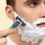 Ao centro da imagem está um homem branco, com cabelos castanhos, de perfil. Sobre seu pescoço, bochechas, buço e queixo há uma espuma de barbear branca. Com a mão ele segura um aparelho de barbear cinza, preto e azul.