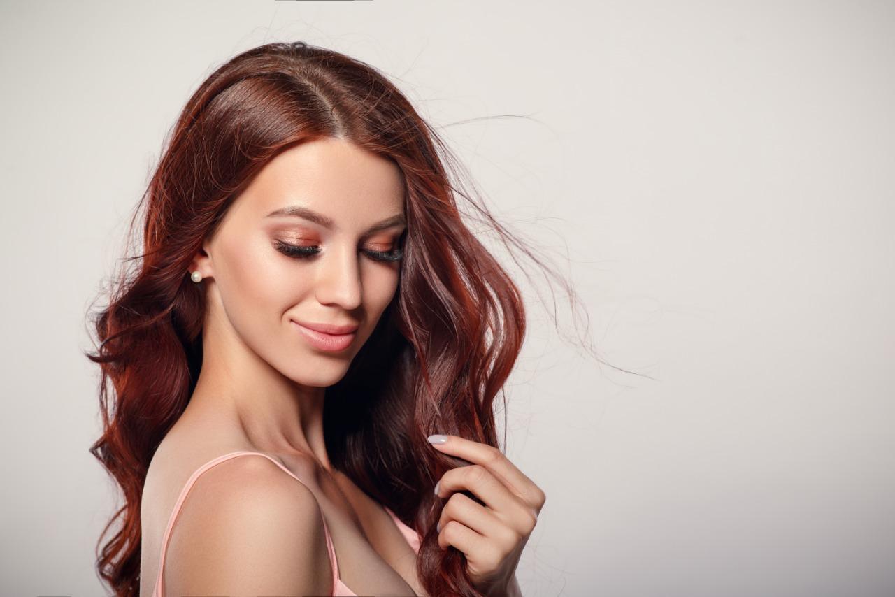 A imagem mostra uma mulher, com cabelos compridos e ruivos. Ela está de olhos fechados e sorri segurando uma mecha de cabelo.